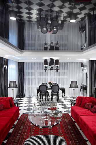 Czerwone sofy i dywan dominujące na tle czerni i bieli